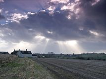 Breaking Through. Landscape shot of a rural cottage in a harvested field with the sun breaking through overhead royalty free stock images