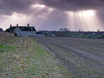 Breaking through 2. Farm cottage in a harvested field with the sun breaking through the clouds stock photo