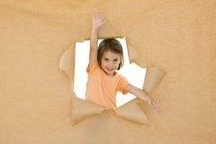 Breaking through. Little girl breaking through a brown paper Royalty Free Stock Photo