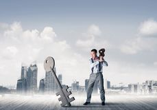 Breaking through access concept with furious man crashing concrete key. Determined businessman against modern cityscape breaking with violin stone key figure royalty free stock photos