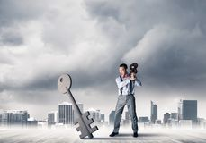 Breaking through access concept with furious man crashing concrete key. Determined businessman against modern cityscape breaking with violin stone key figure royalty free stock images
