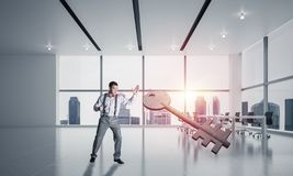 Breaking through access concept with furious man crashing concrete key. Determined businessman in modern interior breaking with fist stone key figure stock image