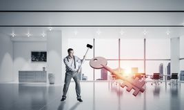 Breaking through access concept with man in crashing concrete key. Determined businessman in modern interior breaking with hammer stone key figure stock photo