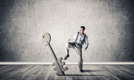 Breaking through access concept with man in room crashing concre. Determined businessman in concrete interior breaking with leg stone key figure. 3D rendering Royalty Free Stock Photography