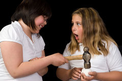 Breaking The Bank. Two children using a hammer to break open a small piggy bank, shot against a black background Royalty Free Stock Images