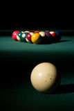 Breaking Billiards. Cue ball ready to be hit into a rack of 8-ball billiard balls on a pool table. Isolated lighting on a dark background Royalty Free Stock Photo