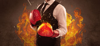 Breaking with boxing. A strong sales person breaking something into pieces with red boxing gloves concept illustrated with glowing residue flying in the air Stock Photos