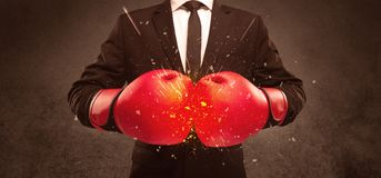 Breaking with boxing. A strong sales person breaking something into pieces with red boxing gloves concept illustrated with glowing residue flying in the air Stock Images