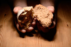 Breaking bread. On a wooden table dark background royalty free stock photography