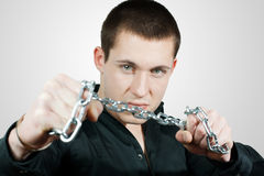 Breaking a chain. Young man wants to break the chains Royalty Free Stock Photography