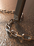 Breaking chains. By chisel concept Royalty Free Stock Image