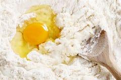 Breaking eggs into flour to make bread dough Stock Photos