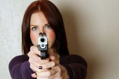 Breaking and Entering. Image of female pointing a gun at somebody breaking and entering Stock Photography