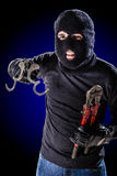 Breaking Free. A burglar jailbreaking with a pair of opened handcuffs in his hand royalty free stock photos