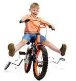 Breaking free. A young boy learning to ride and breaking free from training wheels all isolated on a white background royalty free stock photography