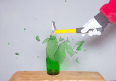 Breaking a glass bottle Stock Images