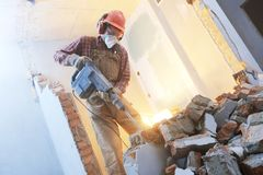 Breaking interior wall. worker with demolition hammer. Interior demolition. Worker with personal protection equipment and demolition hammer at service for brick Stock Photos