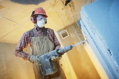 Breaking interior wall. worker with demolition hammer royalty free stock photo