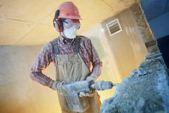 Breaking interior wall. worker with demolition hammer stock photo