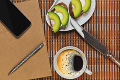 Breaking for the lunch and time planning. Simple sandwiches with spreading cheese and avocado slices, cup with coffee and some planning accessories stock photo