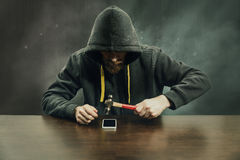 Breaking mobile phone encryption. Hooded hacker breaking mobile phone protection with hammer Royalty Free Stock Photography