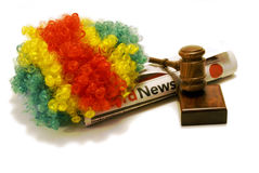 Breaking News On Clowns. An  clowns wig, newspaper, and gavel to illustrate how clowns have been an issue across the nation this year Royalty Free Stock Image