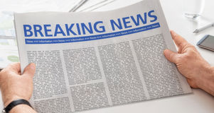 Breaking News. Man reading newspaper with the headline Breaking News royalty free stock photography