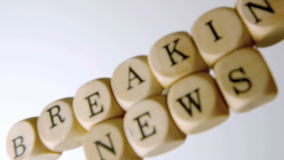 Breaking news spelled out in dice falling on white surface stock video footage