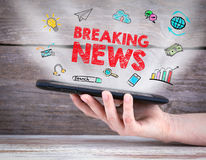 Breaking News. Tablet computer in the hand. Old wooden background Royalty Free Stock Photos