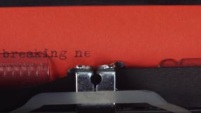 Breaking news - typed on a old vintage typewriter. Printed on red paper. The red paper is inserted into the typewriter stock footage