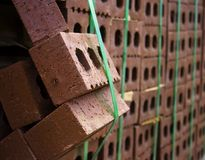 Breaking Out. Stack of red bricks tied with bright lime green bands with one portion of the bricks falling out of the stack as if breaking out of the pack Royalty Free Stock Image