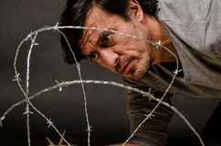 Breaking out. Latino male trying to break through a barbed fence, a conceptual shot Stock Photography