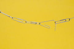 Breaking paperclip chain on yellow Stock Photography