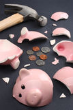 Breaking a piggy bank business & finance concept. Broken piggy bank containing few coins conveying a sense of misery and financial despair. Business & Finance Royalty Free Stock Photography
