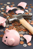 Breaking a piggy bank business & finance concept. Financial savings concept featuring a piggy bank broken by hammer loaded with money. Business & Finance Stock Images
