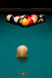 Breaking racked pool balls. White ball is rolling to break the racked billiard balls on the green pool table Stock Photo