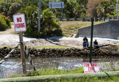 """Breaking the rules. Two men fishing directly behind a """"No Fishing"""" sign Royalty Free Stock Image"""