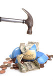 Breaking into savings. Photograph of a hammer smashing a money box to get the money out. shot in studio and isolated on white Royalty Free Stock Photo