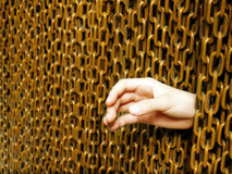 Breaking through security. Break in at high security site! - A concept picture of a hand sneaking through a thick layer of heavy iron chains. Abstract concept of stock image