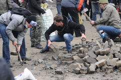 Breaking stones in Kiev, Ukraine. Protesters in Independence Square, Kiev, Ukraine breaking paving stones to defend themselves during the revolution stock photos