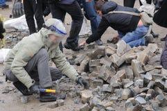 Breaking stones in Kiev, Ukraine. Protester breaking paving stones, in Independence Square Kiev, Ukraine during revolution stock images