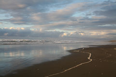 A breaking storm on the beach. Clouds against heavy breaking surf after a storm on the beach reflecting in the water below Royalty Free Stock Images