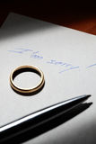 Breaking Up. A note saying I'm sorry! with a wedding ring and a pen over it. A concept about divorce or breaking up of marriage Royalty Free Stock Images