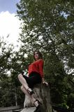 Beautiful woman in red shirt and black skirt is sitting in a sexual pose on the tree stump in the park Stock Photos