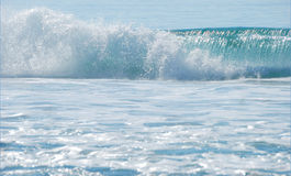 Breaking Wave. Breaking ocean wave shown on a sunny day with foam in the foreground Royalty Free Stock Photos
