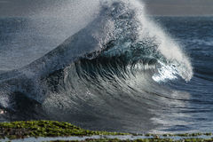 Breaking wave rises up in backwash Stock Photo