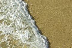 Breaking wave on a sandy beach Stock Photos