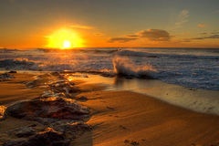 Breaking wave in sunrise seascape. Early morning magic as the sun rises above the horizon transforming the beach and sea Stock Photo