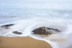 Breaking waves on beach. Gentle waves spilling against rocks on a sandy beach in the early morning in tropical Queensland Australia Stock Image