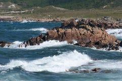 Breaking waves crashing into granite rocks. Royalty Free Stock Images